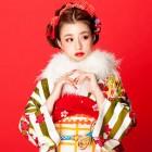 赤い背景に白いファーが映える古典スタイルの振袖姿の女の子の写真